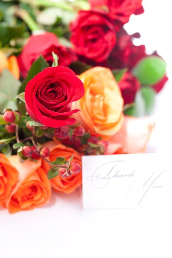 Las rosas coloridas y una tarjeta con las palabras le agradecen imagen de archivo libre de regalías