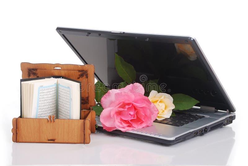 Las rosas hermosas computadora portátil y el libro sagrado del Islam pusieron t foto de archivo
