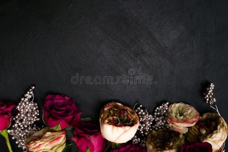 Las rosas rosadas rojas platean el fondo floral oscuro de la decoración imagen de archivo libre de regalías