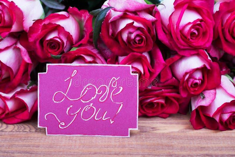 Las rosas y la tarjeta de felicitación le aman fotos de archivo libres de regalías