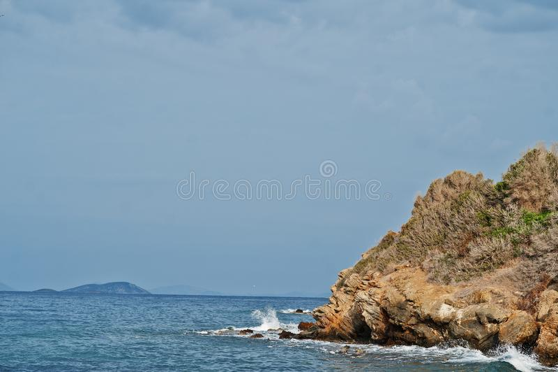 Las roturas de la onda del mar en rocas de la playa ajardinan Las ondas del mar se estrellan y salpican en rocas en Bodrum, Turqu foto de archivo