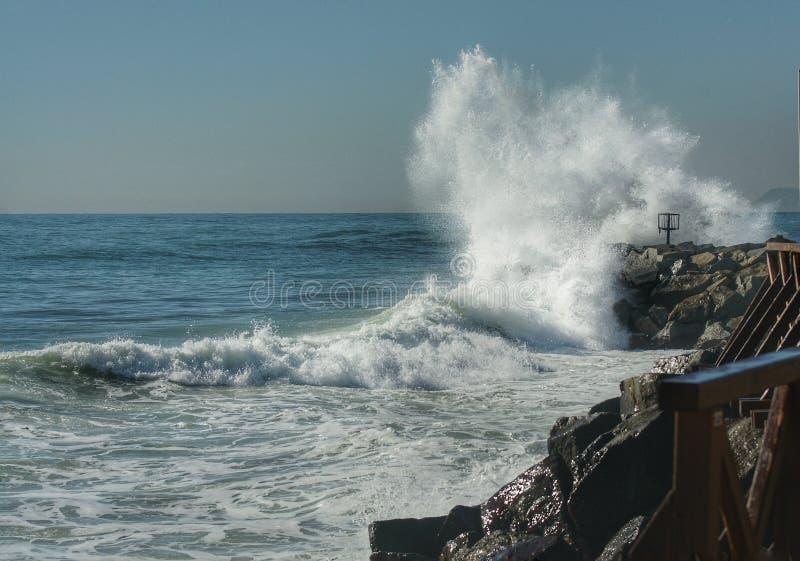 Las roturas de la onda en las rocas foto de archivo