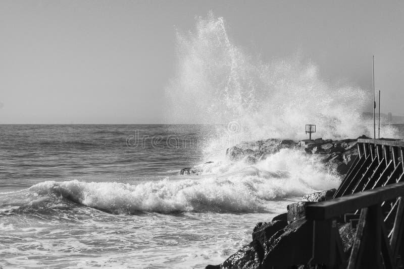 Las roturas de la onda en las rocas imagenes de archivo