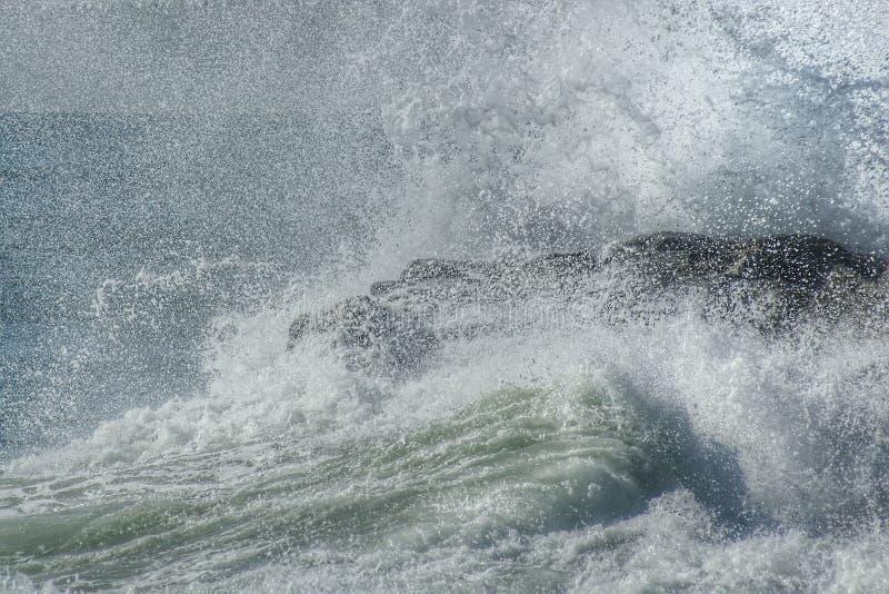 Las roturas de la onda en las rocas fotos de archivo