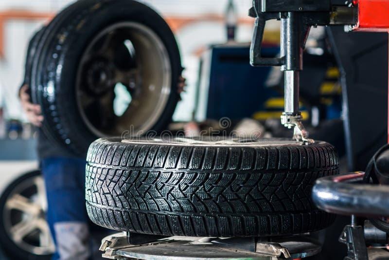 Las ruedas de cambios del mecánico a un coche moderno fotos de archivo libres de regalías