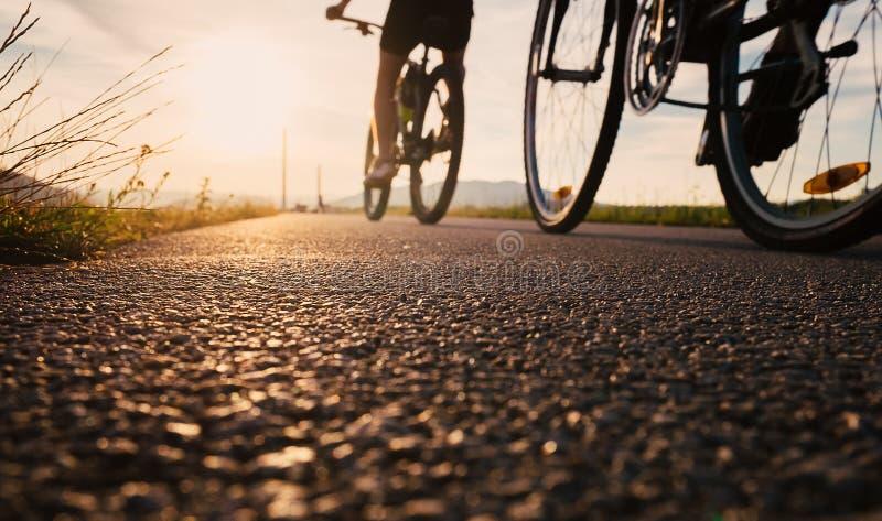 Las ruedas de la bici se cierran encima de imagen en el camino de la puesta del sol del asfalto imagen de archivo