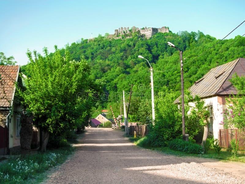 Las ruinas de la fortaleza de Khust en una colina en el medio de un pueblo ucraniano típico Restos de las paredes de una piedra m fotografía de archivo