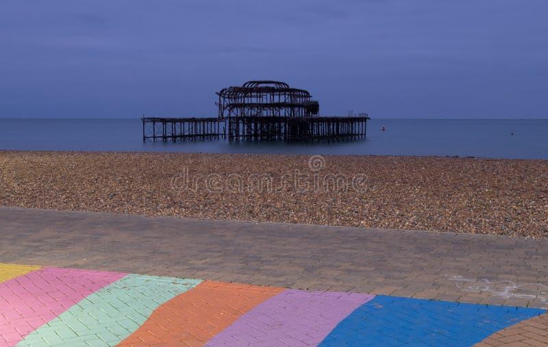 Las ruinas del embarcadero del oeste, Brighton, East Sussex, Reino Unido En el primero plano, el Pebble Beach y el pavimento pint foto de archivo libre de regalías