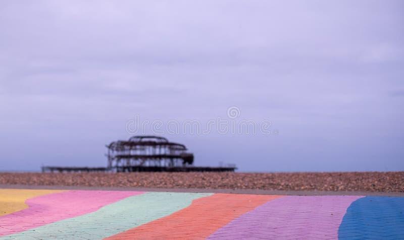Las ruinas del embarcadero del oeste, Brighton, East Sussex, Reino Unido En el primero plano, el Pebble Beach y el pavimento pint imagenes de archivo