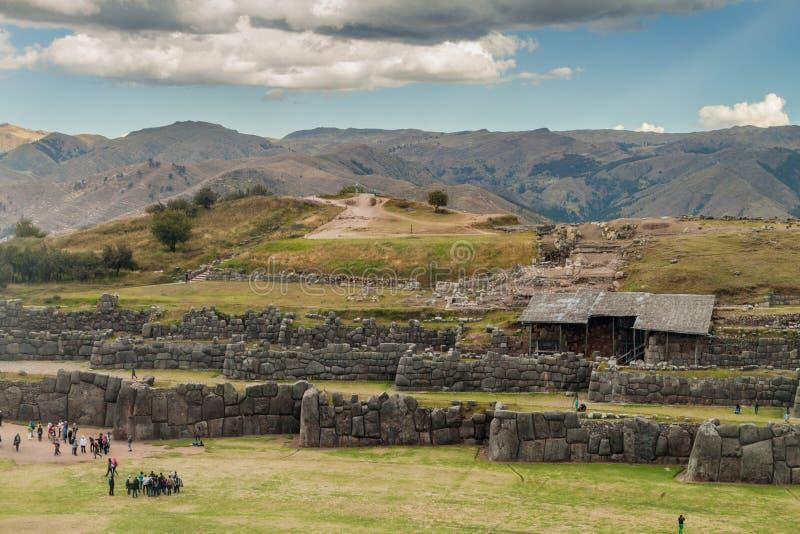 Las ruinas del inca de la visita de los turistas de Sacsaywaman cerca de Cuzco foto de archivo libre de regalías