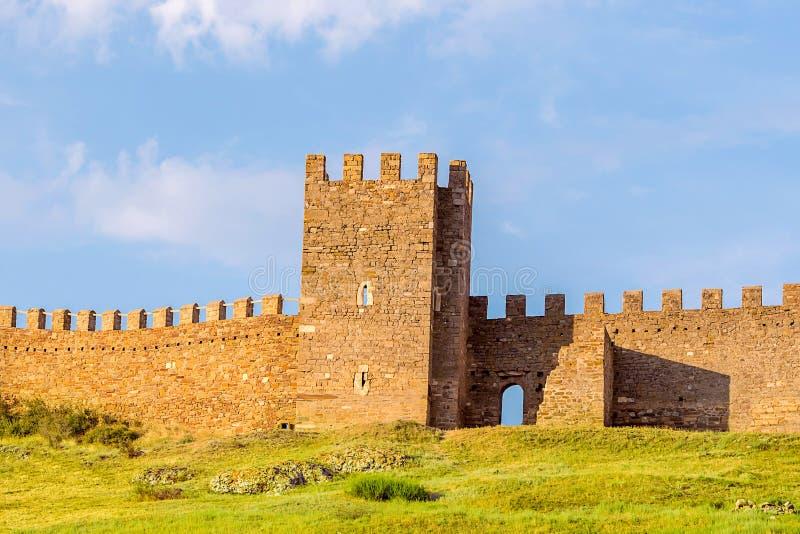 Las ruinas Genoese de la fortaleza de la torre vieja crenellated la pared en la cima de un paseo de la colina verde a través de e fotografía de archivo libre de regalías