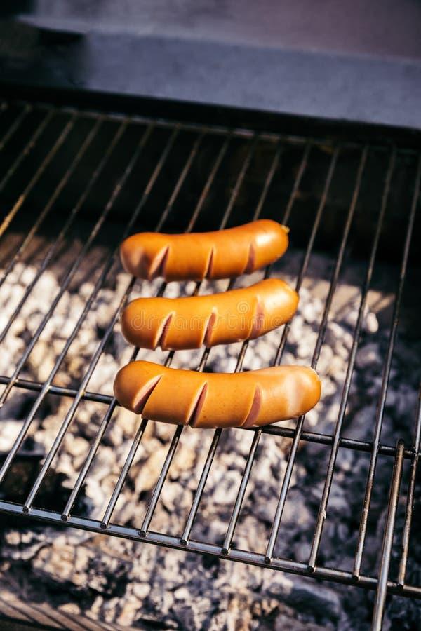Las salchichas calientes cocinaron al aire libre en parrilla sobre los carbones fotos de archivo libres de regalías