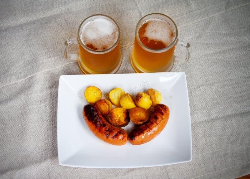 Las salchichas de cerdo en una placa blanca, tazas de cerveza, asaron las patatas fotografía de archivo libre de regalías