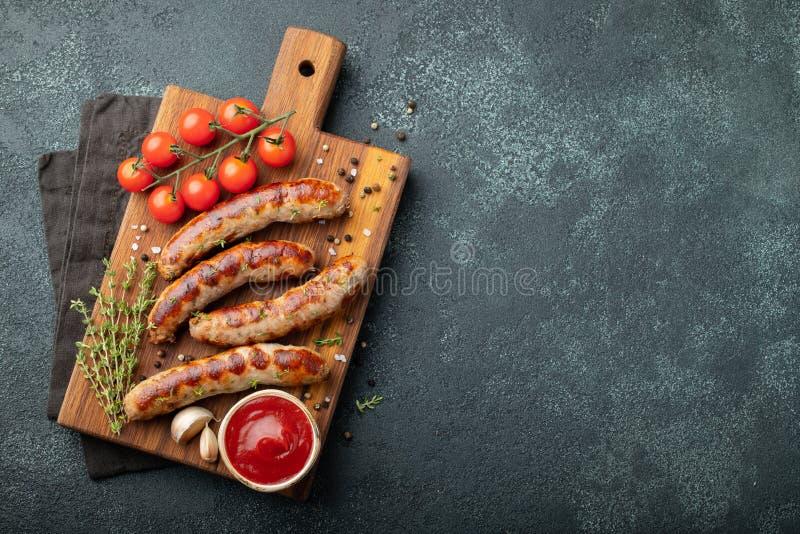 Las salchichas fritas con las salsas y las hierbas en una porción de madera suben Gran bocado de la cerveza en un fondo oscuro Vi fotos de archivo