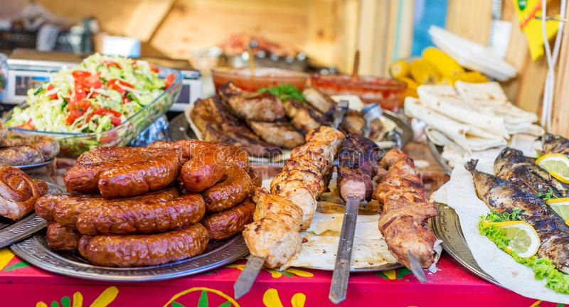 Las salchichas, kebab, frieron los pescados y la otra comida en el festival de la comida de la calle foto de archivo