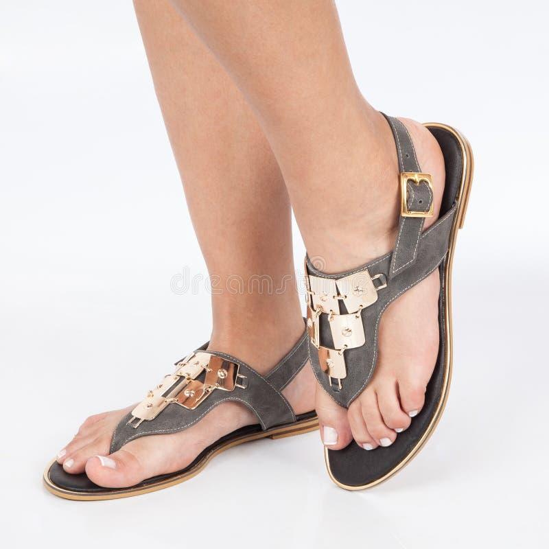 Las sandalias de cuero grises con oro aplicaron en pies el mujere en el fondo blanco imagenes de archivo