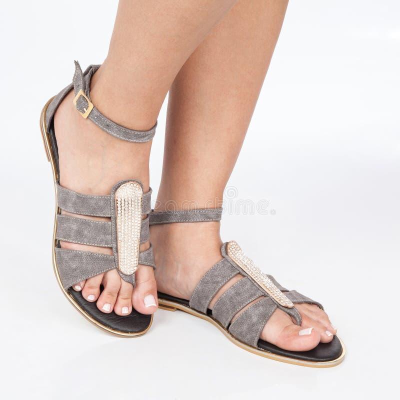 Las sandalias de cuero grises con oro aplicaron en pies el mujere en el fondo blanco foto de archivo