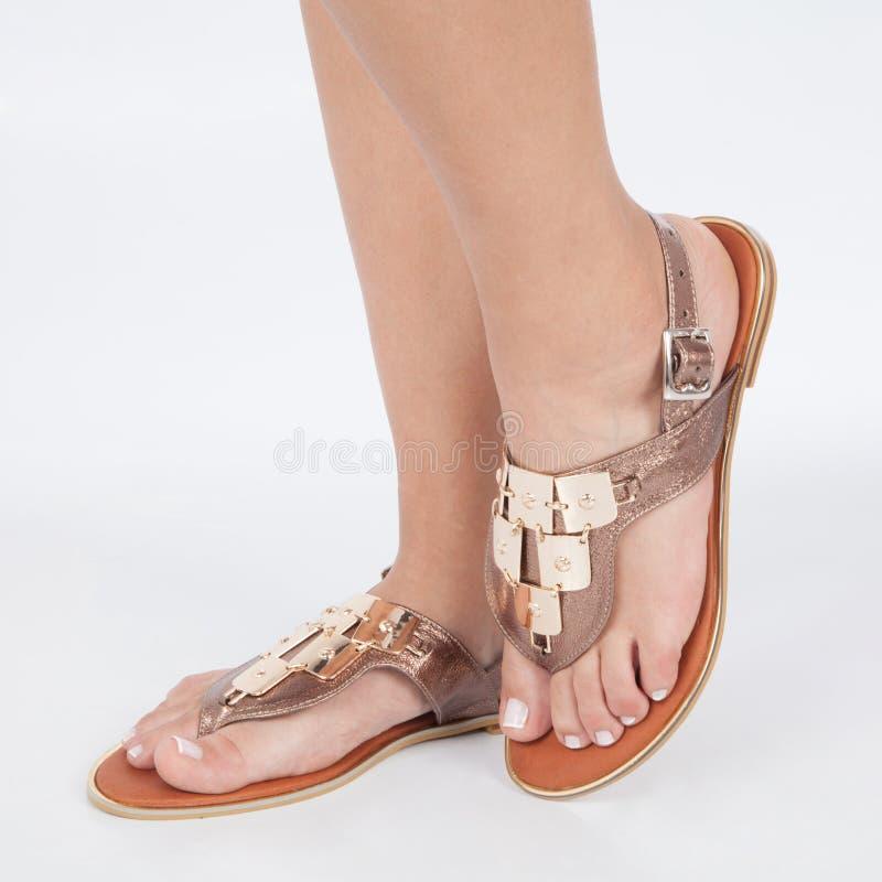 Las sandalias de cuero marrones brillantes con oro aplicaron en pies el mujere en el fondo blanco imágenes de archivo libres de regalías