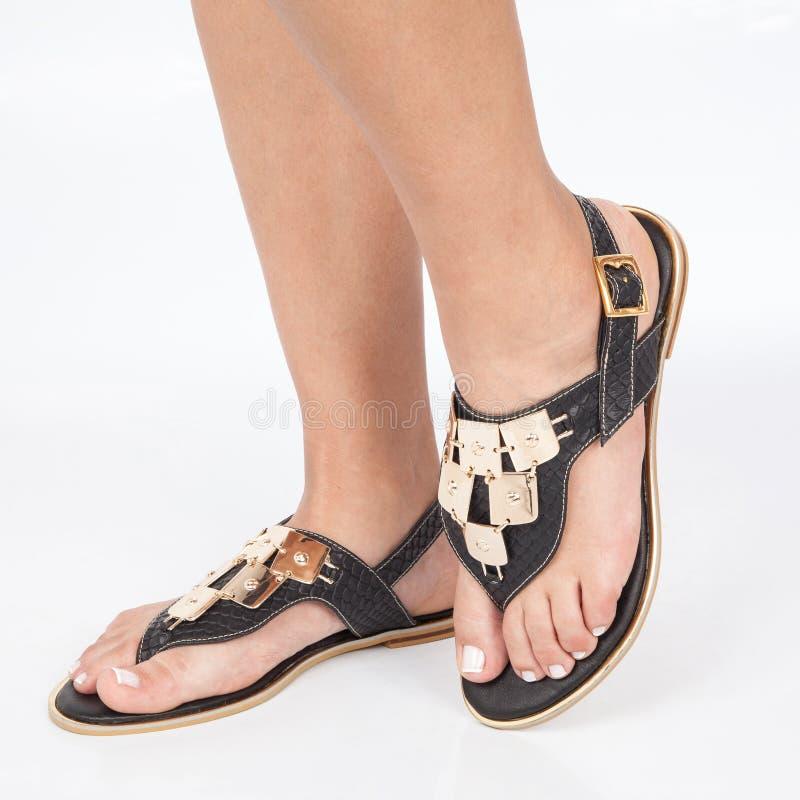 Las sandalias de cuero negras con oro aplicaron en pies el mujere en el fondo blanco imágenes de archivo libres de regalías