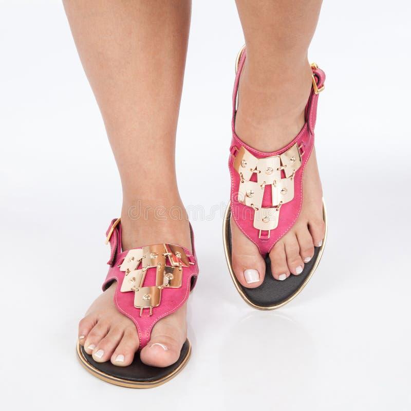 Las sandalias de cuero rosadas oscuras con oro aplicaron en pies el mujere en el fondo blanco foto de archivo libre de regalías