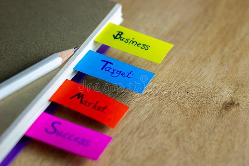 Las señales coloridas se escriben para el negocio, blanco, mercado, éxito, y tienen un lápiz blanco imágenes de archivo libres de regalías