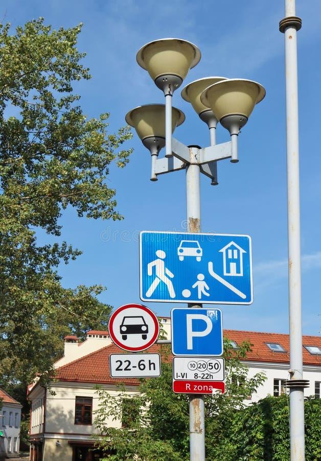 Las señales de tráfico de la zona automotriz urbana roja cuelgan en una fuga de la calle fotos de archivo libres de regalías