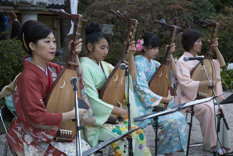 Las señoras congriegan en el kimono que toca el instrumento musical del biwa para la observación de Hakata Tomyo fotografía de archivo libre de regalías