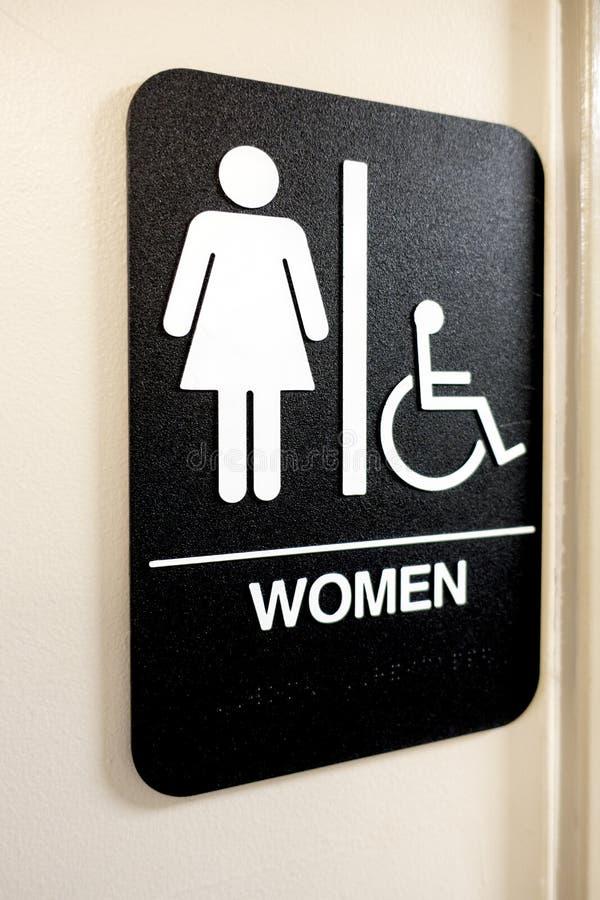 Las señoras y la silla de ruedas tienen acceso a la muestra y a iconos del cuarto de baño fotos de archivo libres de regalías