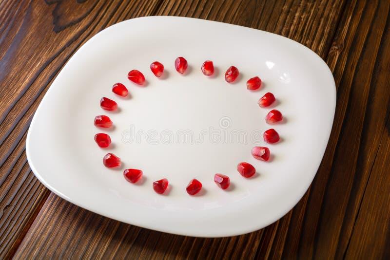 Las semillas de la granada en la forma de círculo en la placa blanca en rústico cortejan fotografía de archivo