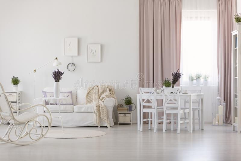 Las sillas blancas en la mesa de comedor en interior del apartamento con la manta en el sofá y el rosa cubren Foto verdadera imagenes de archivo