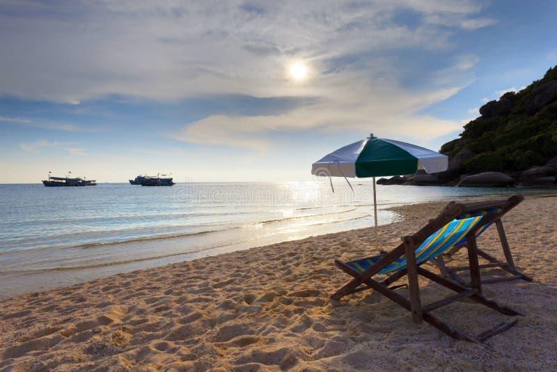 Las sillas de madera varan en la cara de mar y el conjunto del sol fotos de archivo