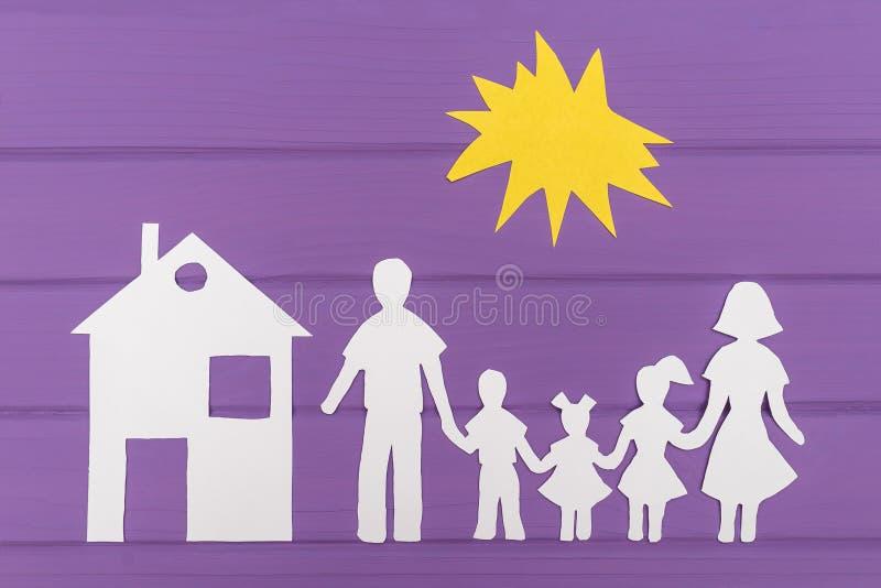 Las siluetas cortaron del papel del hombre y de la mujer con dos muchachas y el muchacho debajo del sol, casa cerca foto de archivo