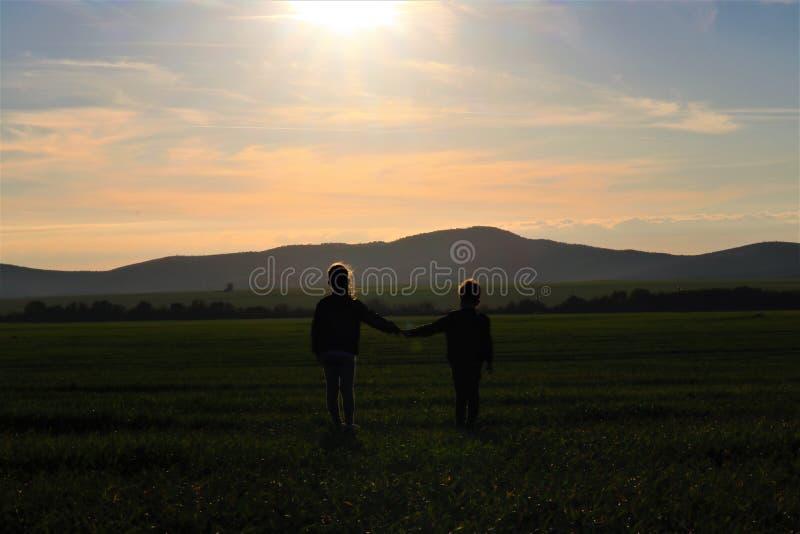 Las siluetas de dos pequeños niños están mirando la puesta del sol hermosa foto de archivo libre de regalías