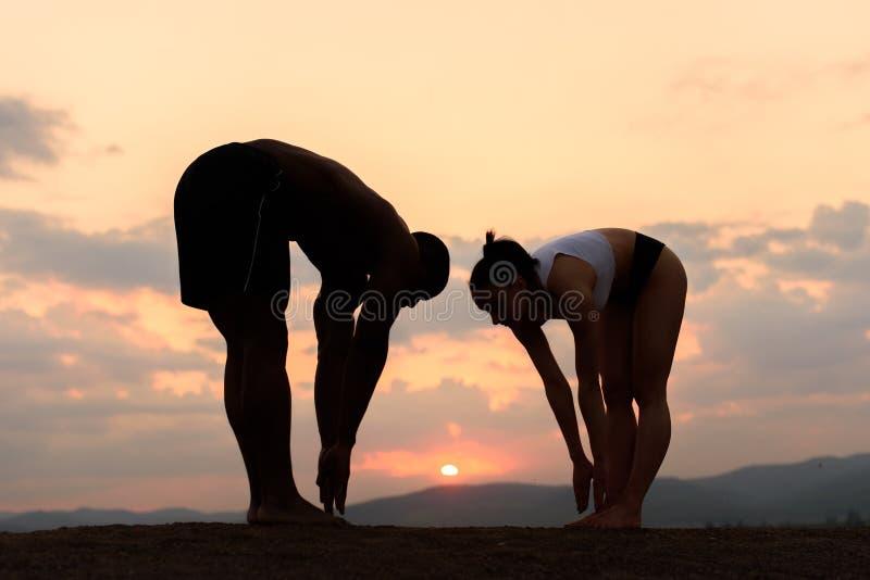 Las siluetas de la raza mixta juntan estirar y el entrenamiento juntas en el fondo de las montañas rocosas con puesta del sol de  fotos de archivo libres de regalías