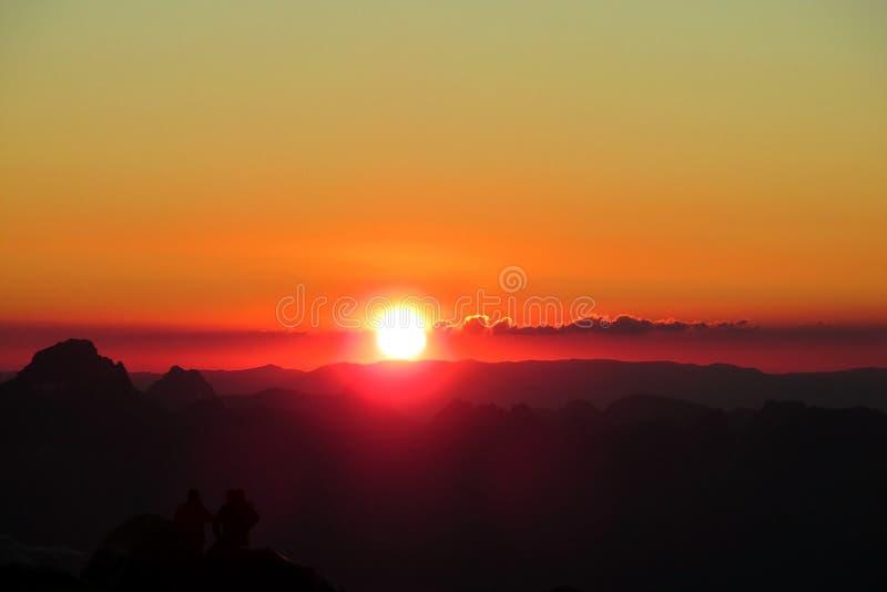 Las siluetas de las tiendas de la hormiga de la gente en las montañas en la puesta del sol se encienden foto de archivo