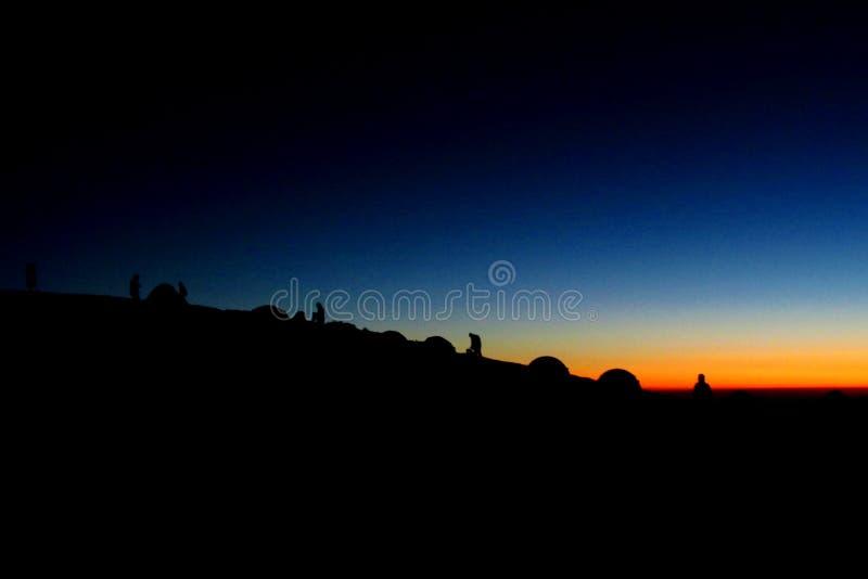 Las siluetas de las tiendas de la hormiga de la gente en las montañas en la puesta del sol se encienden imagen de archivo