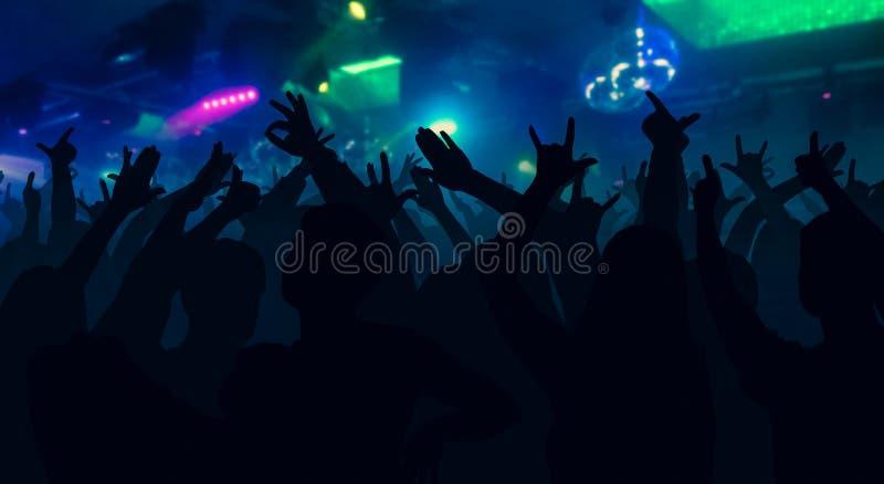 Las siluetas del concierto aprietan con las manos aumentadas en un disco de la música imagenes de archivo