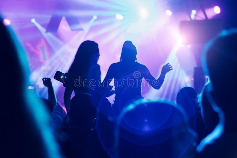 Las siluetas del concierto aprietan delante de luces brillantes de la etapa imagenes de archivo