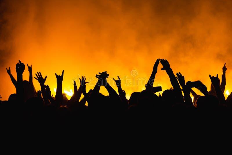 Las siluetas del concierto aprietan delante de luces brillantes de la etapa Gente de baile con las manos encendido contra luz de  fotografía de archivo libre de regalías