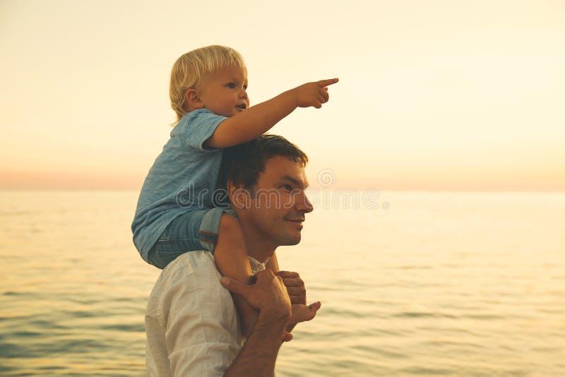 Las siluetas del padre y del hijo en la puesta del sol en un mar varan imagen de archivo libre de regalías