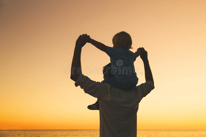Las siluetas del padre y del hijo en la puesta del sol en un mar varan imágenes de archivo libres de regalías