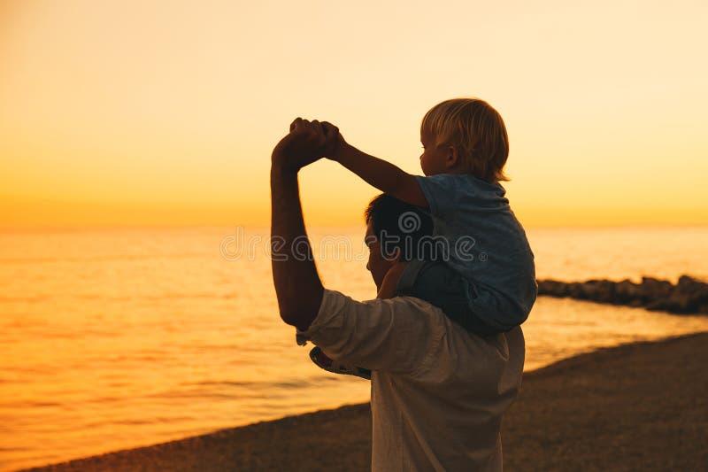 Las siluetas del padre y del hijo en la puesta del sol en un mar varan foto de archivo libre de regalías
