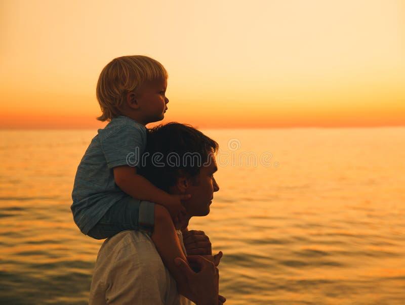 Las siluetas del padre y del hijo en la puesta del sol en un mar varan fotografía de archivo