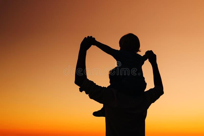 Las siluetas del padre y del hijo en la puesta del sol en un mar varan fotografía de archivo libre de regalías