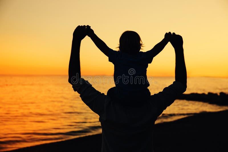 Las siluetas del padre y del hijo en la puesta del sol en un mar varan foto de archivo