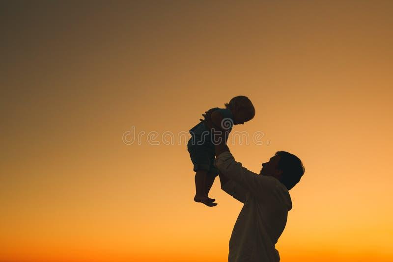 Las siluetas del padre y del hijo en la puesta del sol en un mar varan fotos de archivo libres de regalías