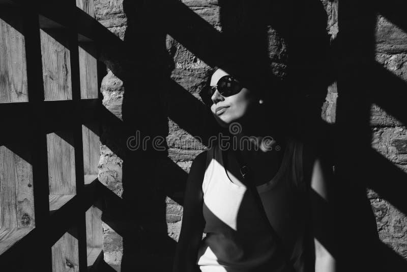Las sombras caen a través de la puerta en la mujer cerca de la pared de ladrillo fotos de archivo libres de regalías