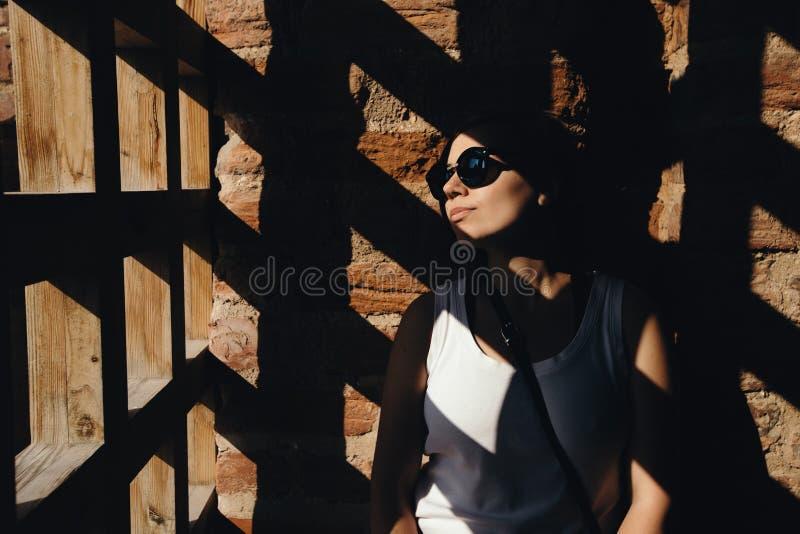 Las sombras caen a través de la puerta en la mujer cerca de la pared de ladrillo imagenes de archivo