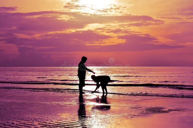 Las sombras de hombres y de mujeres están caminando en la playa en la salida del sol imagenes de archivo