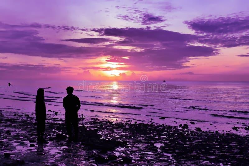 Las sombras de hombres y de mujeres están mirando el sol el subir en la playa foto de archivo